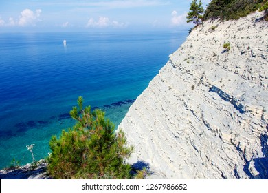 steep steep cliffs, pine trees, yacht in the clear sea, the coast of Gelendzhik, Sosnovka beach, Gelendzhik, Black sea