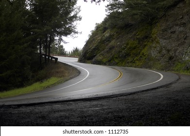 A steep corner on a wet winding road