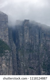 Steep dark Preikestolen cliff grows from ground of the Lysefjorden and reaches low clouds, Rogaland, Norway