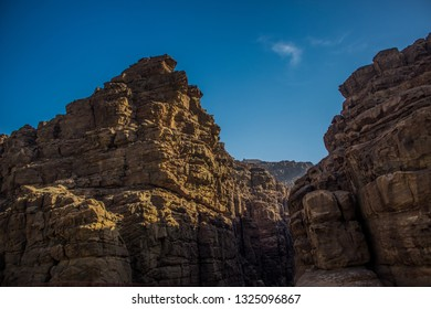 steep desert bare mountain rocks in canyon environment foreshortening from below on blue sky background