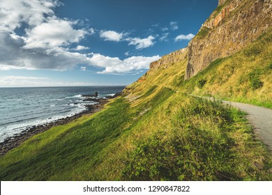 Steep green slope with tourist path. Northern Ireland. The grass covered hill next to the ocean. Overwhelming Irish shoreline scene. Blue cloudy sky background. Perfect touristic site.