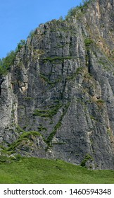 Steep high cliff overgrown with small grass, Shaman Mountain, a sacral place in the Altai Mountains. Siberia, Russia.