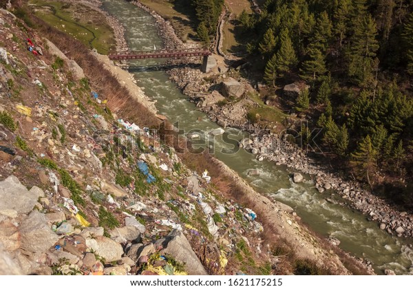 A steep hillside sloping down to the Baspa river littered with plastic trash thrown by tourists in the village of Chitkul in Himachal Pradesh, India.