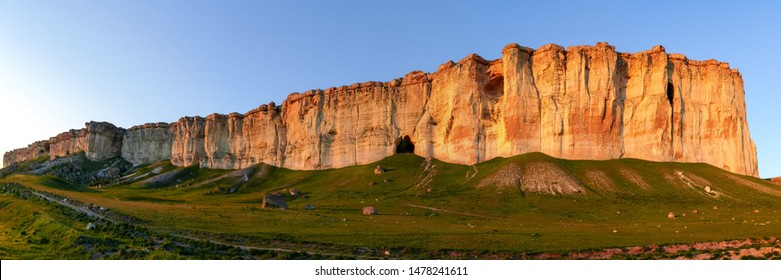 Steep limestone rock on edge of the plateau on a background of clear sky at sunset, panoramic view from a foot of the mount