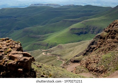 steep mountain pass with vista of mountains and green hills in the dis