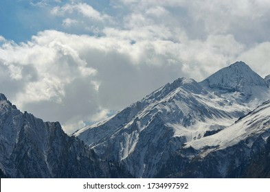 Steep mountain peaks are covered in snow. Some trees are on the lower slopes. Sunlight falls onto the snow, but the sky is filled with storm clouds.