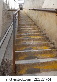 Steep old weathered concrete stairs with cement brick walls & rusty water marks from the metal handrail. The steep stair case creates a perspective & contrast between smooth concrete & rusty textures