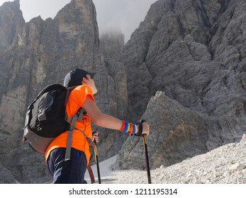 Steep path, Teenage Boy facing a rockface in the mointains