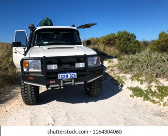Steep Point, Western Australia / Australia - 20 August 2018: Rugged ute, 4WD vehicle on sandy track at Steep Point, Western Australia beach with green scrub bushes, sand and clear blue sky.