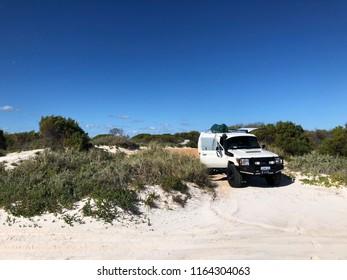 Steep Point, Western Australia / Australia - 20 August 2018: 4WD vehicle on sandy track at Steep Point, Western Australia beach with green scrub bushes, sand and clear blue sky.