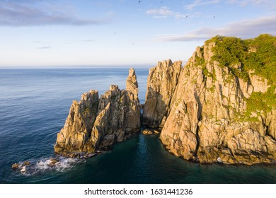 Steep rocks with cracks on sea coast at sunrise. Aerial view of Cape Babkina at Gamov Peninsula. Seaside nature scenery in Primorsky Krai, Far East, Russia