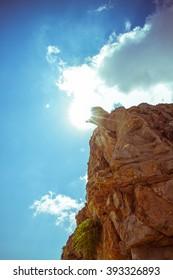 Steep rocks with place against backlight sun sky as background