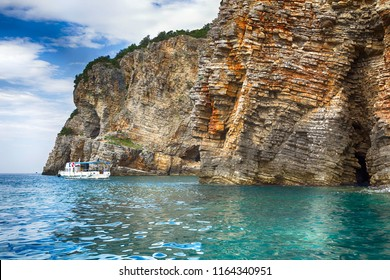 Steep rocky coast and a pleasure boat with tourists in the sea