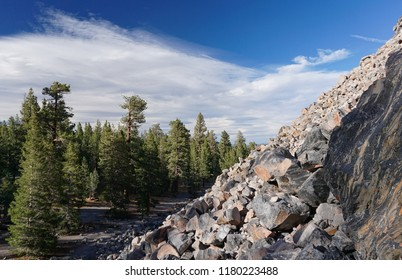 The steep, rocky slope of Obsidian Dome in California's Sierra Nevada mountains, towering above a border of Ponderosa pines, is at 8,000 feet elevation. White clouds in a blue sky.