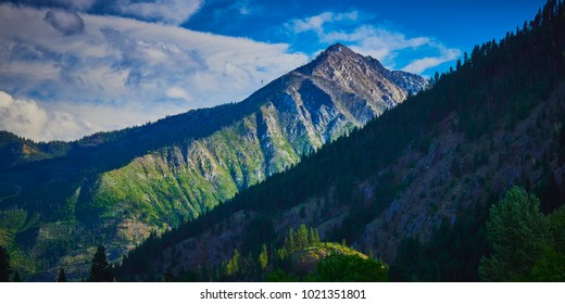 Steep and rugged mountain view in late afternoon with blue sky and wispy clouds near Leavenworth Washington