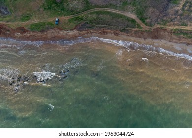 Steep sea shore and surf. Sea water muddy with sand after storm and algae. Aerial view
