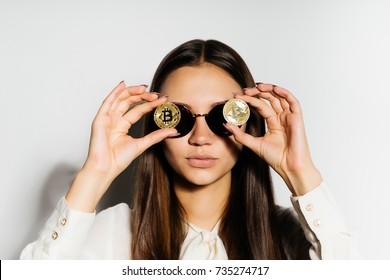 steep, serious girl with black glasses put a coin to her eyes.bitcoins, isolated