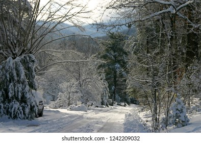 A steep, snow covered road in North carolina with mountains in the distance