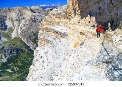 "Steep stone wall and remote climber traversing along the steel cable of via ferrata ""Lipella"", Tofana massif, Dolomite Alps, Italy"