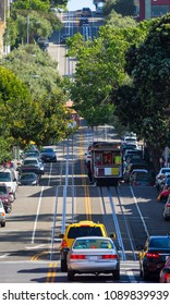 Steep street in San Francisco with cable cars during day time