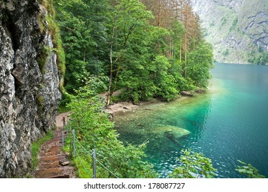 Steep Trail with Stairs at Lake Obersee, Bavaria, Germany. View on the Lake with intense green Water.