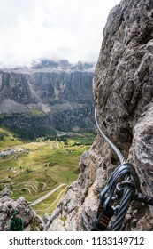 steep Via Ferrata in the Dolomites of Alta Badia in northern Italy with carabiners clicked into the steel cable and clamps for safety