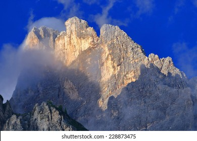 Steep walls of Monte Cristallo embedded in clouds at sunset, Dolomite Alps, Italy