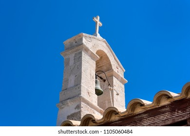 Steeple with bronze tower bell and cross on top of old small church chapel with blue sky in the background - concept Christianity religion god faith tradition architecture history sign Jesus Christ