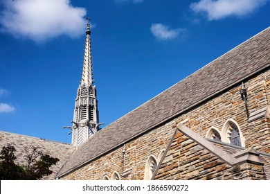 The steeple and exterior of the loyola alumni memorial chapel on the evergreen campus at loyola university Baltimore Maryland on a sunny blue sky day.