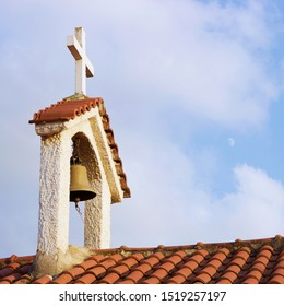 Steeple on top of the roof of christian orthodox byzantine Greek church. Big bronze bell, red roof tiles and a big white cross, background view of blue cloudy sky and figure of moon