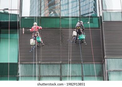 steeplejack workers washing windows in the office building. climbers wash windows and glass facade of the skyscraper