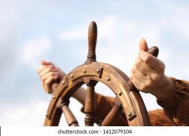 Steering hand wheel ship on sky background, hand hold hand wheel