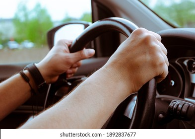 The steering wheel of the car is in the hands of a man while traveling