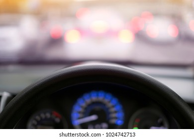 steering wheel close up with blur road and traffic jam