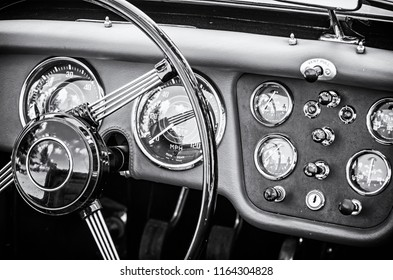 Steering wheel and dashboard in historic vintage red car. Retro automobile interior scene. Old vehicle. Driving theme. Black and white photo.