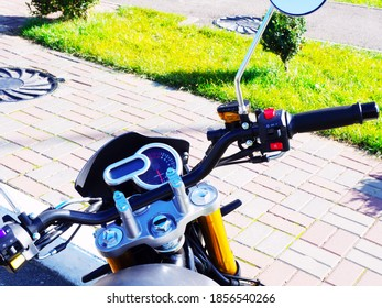 The steering wheel of a motorcycle is standing on the sidewalk on a sunny day