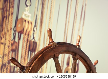 Steering wheel on the old ship as wallpaper for your romantic sea cruise under sails in retro style. Marine equipment with a skipper helm on blur background of ancient sailing vessel.