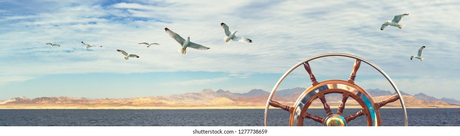 Steering wheel on sailing ship at coastal landscape background for your concept of marine adventure. Wide billboard with flying seagulls over the sea, clouds and mountains on skyline.