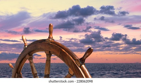 Steering wheel on the ship at sunset background. Skipper's wheel on an old ship. Ship rudder on the yacht, side view.