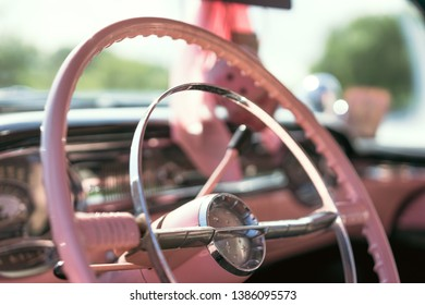 Steering wheel of a pink classic car