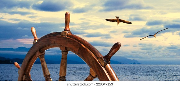Steering wheel at sea background.  Skipper's wheel on an old ship. Sea voyage at the seaside with captains wheel of the old vessel, closeup. Marine skyline on the sundown with two seagull on the sky.