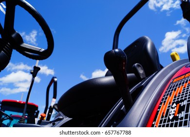 The steering wheel, seat and gear shifters of a brand new tractor on a bright sunny day with a blue sky.