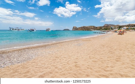 Stegna beach with sunshades, sunbeds and boats in background (RHODES, GREECE)