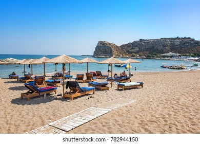 Stegna beach with sunshades and sunbeds, boats in background (RHODES, GREECE)