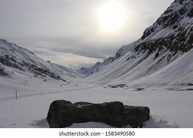 Großer Stein zum Meditieren im Vordergrund und Bergpanorama im Hintergrund mit hochstehender großer Sonne die durch die dichte Wolkendecke ins Tal scheint