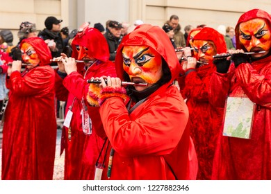 Steinenberg, Basel, Switzerland - February 19th, 2018. Close-up of carnival participants in bright red costumes playing piccolo flute