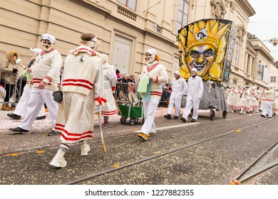 Steinenberg, Basel, Switzerland - February 19th, 2018. Group of carnival participants in classic tennis costumes with their main lantern