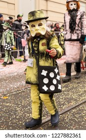 Steinenberg, Basel, Switzerland - February 19th, 2018. Close-up of a child in costume distributing sweets during the parade