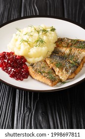 Stekt stromming or fried herring is a hearty Swedish food with boiled potatoes closeup in the plate on the table. Vertical - Shutterstock ID 1998697811