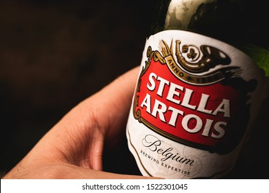 Stella Artois, beer. Photograph of a man holding a beer bottle of Belgian company Stella Artois with dark background. Brasilia, Federal District - Brazil. Circa - September, 2019.